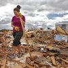 Miranda Lewis smiles as she recovers the height growth marker for her six-year-old son Copper among the rubble left behind after the home was destroyed by Tuesday\'s tornado west of El Reno, Wednesday, May 25, 2011. Photo by Chris Landsberger, The Oklahoman