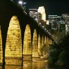 Photo - FILE - In this Oct. 17, 2005 file photo, the Minneapolis skyline is illuminated in the background from the historic Stone Arch Bridge over the Mississippi River.  (AP Photo/Jim Mone,File)