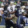 Photo - Seattle Seahawks defensive end Michael Bennett (72) and defensive end Cliff Avril (56) sack New Orleans Saints quarterback Drew Brees (9) during the third quarter of an NFC divisional playoff NFL football game in Seattle, Saturday, Jan. 11, 2014. (AP Photo/Elaine Thompson)