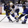 Photo - Buffalo Sabres' Zemgus Girgensons (28), of Latvia, chases after a loose puck alongside St. Louis Blues' Dmitrij Jaskin, left, of Russia, and Kevin Shattenkirk, right, during the first period of an NHL hockey game on Thursday, April 3, 2014, in St. Louis. (AP Photo/Jeff Roberson)