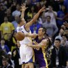 Photo - Los Angeles Lakers' Steve Nash (10) passes next to Golden State Warriors' Stephen Curry (30) during the second half of an NBA basketball game in Oakland, Calif., Saturday, Dec. 22, 2012. Los Angeles won in overtime 118-115. (AP Photo/Marcio Jose Sanchez)