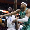 Photo - Boston Celtics' Paul Pierce, right, passes the ball under pressure from Charlotte Bobcats' Bismack Biyombo (0) in the first quarter of an NBA basketball game in Boston, Saturday, March 16, 2013. (AP Photo/Michael Dwyer)