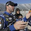 Jimmie Johnson talks to team members after winning the pole for Sunday\'s NASCRA Sprint Cup auto race at Martinsville Speedway in Martinsville, Va., Friday, April 5, 2013. (AP Photo/Steve Helber)