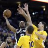 San Antonio Spurs\' Tony Parker, left, shoots between Golden State Warriors\' David Lee (10) and Klay Thompson, right, during the first half of an NBA basketball game Friday, Feb. 22, 2013, in Oakland, Calif. (AP Photo/Ben Margot)