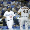 Photo - San Francisco Giants starting pitcher Madison Bumgarner, right, and Los Angeles Dodgers' Yasiel Puig, left, exchange words as Puig runs down the third base line after hitting a solo home run during the sixth inning of a baseball game, Friday, May 9, 2014, in Los Angeles. (AP Photo/Danny Moloshok)