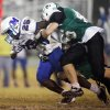 Sheldon Bulock (25) of Millwood is brought down by Drew Neuberger (46) and a second McGuinness defender during a high school football game between Millwood and Bishop McGuinness at Bishop McGuinness Catholic High School in Oklahoma City, Friday, Sept. 16, 2011. Photo by Nate Billings, The Oklahoman