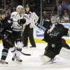 San Jose Sharks goalie Antti Niemi, of Finland, right, hits Los Angeles Kings center Trevor Lewis (22) with his stick next to Sharks center Dominic Moore (18) during the second period of an NHL hockey game Saturday, April 7, 2012 in San Jose, Calif. (AP Photo/Marcio Jose Sanchez)