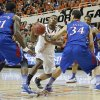Oklahoma State \'s Marcus Smart (33) drives past Kansas\' Jamari Traylor (31) and Perry Ellis (34) during the college basketball game between the Oklahoma State University Cowboys (OSU) and the University of Kanas Jayhawks (KU) at Gallagher-Iba Arena on Wednesday, Feb. 20, 2013, in Stillwater, Okla. Photo by Chris Landsberger, The Oklahoman