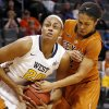 Photo - Texas guard Celina Rodrigo, right, reaches in to try and take the ball away from West Virginia center Asya Bussie (20) in the first half of an NCAA college basketball game in the semifinals of the Big 12 Conference women's college tournament in Oklahoma City, Sunday, March 9, 2014. (AP Photo/Sue Ogrocki)