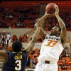 Photo - Oklahoma State's Marcus Smart (33) shoots against West Virginia's Juwan Staten (3) during an NCAA men's basketball game between Oklahoma State University (OSU) and West Virginia at Gallagher-Iba Arena in Stillwater, Okla., Saturday, Jan. 26, 2013. Photo by Nate Billings, The Oklahoman