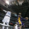 Dallas Mavericks\' O.J. Mayo (32) defends as Los Angeles Lakers\' Kobe Bryant goes up for a reverse layup score in the first half of an NBA basketball game Sunday, Feb. 24, 2013, in Dallas. (AP Photo/Tony Gutierrez)