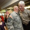 Garry McKinnis, right, under sheriff with the Payne County sheriff\'s department, hugs Cpl. Scott Hopper after Hopper arrived to a surprise welcome from supporters at Will Rogers World Airport in Oklahoma City, Friday, Oct. 28, 2011. At lower left is Cpl. Scott Hopper\'s wife, Donella Hopper. Cpl. Scott Hopper is a Payne County sheriff\'s deputy who has returned to Oklahoma for OSU\'s homecoming. Hopper was injured in Afghanistan while serving in the National Guard and has been recovering in a San Antonio hospital. Photo by Nate Billings, The Oklahoman