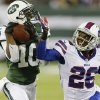 Photo - New York Jets' Santonio Holmes (10) catches a pass for a touchdown as Buffalo Bills defensive back Justin Rogers (26) defendsn during the second half of an NFL football game Sunday, Sept. 22, 2013, in East Rutherford, N.J. (AP Photo/Seth Wenig)
