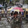 Photo -   Residents negotiate a flooded street at Obando town, Bulacan province, north of Manila, Philippines on Tuesday July 31, 2012. Typhoon Saola dumped torrents of rain as it swept past the Philippines, killing at least seven people and displacing more than 20,000 others by Tuesday. (AP Photo/Aaron Favila)
