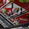 Photo - Shoppers take escalators under the logo of Nintendo and Super Mario characters at an electronics store in Tokyo Wednesday, May 7, 2014. Nintendo Co. sank to a loss for the fiscal year ended March as sales of its Wii U game machine continued to lag, but the Japanese manufacturer of Pokemon and Super Mario games promised Wednesday to return to profit this year. (AP Photo/Shizuo Kambayashi)