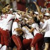 Photo - The OU Sooners surround Lauren Chamberlain (44), middle, after Chamberlain hit the game-winning home run in the twelfth inning during Game 1 of the Women's College World Series NCAA softball championship series between Oklahoma and Tennessee at ASA Hall of Fame Stadium in Oklahoma City, Monday, June 3, 2013. OU won 5-3 in 12 innings. Photo by Nate Billings, The Oklahoman