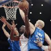 New York Knicks\' Ronnie Brewer (11) splits Dallas Mavericks\' Brandan Wright (34) and Chris Kaman (35) during the first half of an NBA basketball game Friday, Nov. 9, 2012, in New York. (AP Photo/Frank Franklin II)