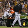 Photo - Miami Marlins relief pitcher Dan Jennings, center, waves as he is driven off the field  after being hit by a line drive off the bat of Pittsburgh Pirates' Jordy Mercer during the seventh inning of a baseball game in Pittsburgh Thursday, Aug. 7, 2014.   (AP Photo/Gene J. Puskar)