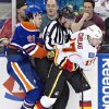 Photo - Calgary Flames Blake Comeau (17) checks Edmonton Oilers Magnus Paajarvi (91) into linesman David Brisbois during second period NHL hockey action in Edmonton, Alberta, on Monday April 1, 2013. (AP Photo/The Canadian Press, Jason Franson).