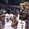 Photo - Chicago Bulls' Carlos Boozer (5) scores on Toronto Raptors' Patrick Patterson and Kyle Lowry during the first half of an NBA basketball game, Wednesday, Feb. 19, 2014 in Toronto. (AP Photo/The Canadian Press, Chris Young)