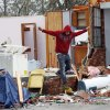 Jay Aycock, 33, of Petal, Miss., leaps from the raised floor of what remains of his aunt\'s kitchen to the ground Tuesday, Feb. 12, 2013 following the Sunday afternoon tornado that caused damage throughout the community. Aycock, who helped his aunt recover some of her personal items, was not affected by the tornado. (AP Photo/Rogelio V. Solis)
