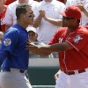 Photo - Chicago Cubs' Anthony Rizzo is held back by Cincinnati Reds' Alfredo Simon (31) at the start of a bench clearing scuffle in the 10th inning of a baseball game, Thursday, July 10, 2014, in Cincinnati. Chicago won 6-4 in 12 innings. (AP Photo/Al Behrman)