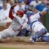 Photo - St. Louis Cardinals' Jon Jay scores past Chicago Cubs catcher Welington Castillo during the seventh inning of a baseball game Saturday, July 26, 2014, in Chicago. (AP Photo/Andrew A. Nelles)