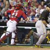 Photo - Pittsburgh Pirates' Russell Martin, right, runs away from Philadelphia Phillies' catcher Carlos Ruiz, left, during the fourth inning of an exhibition baseball game, Friday, March 28, 2014, in Philadelphia. Martin was out trying to score on a single by Travis Ishikawa, (AP Photo/Chris Szagola)