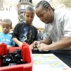 Carl Wright of Oklahoma City helps his sons Kaleb, 7, left, and Josiah, 9, build pieces of R2-D2 during a master build event for the Lego store grand opening, Friday, July 24, 2009, at Penn Square Mall in Oklahoma City. Photo by Sarah Phipps,The Oklahoman