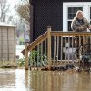 After wading through his flooded front yard, Mike VanBlair opens the front door of his home on North Shore Drive in Moline, Ill. on Monday, April 22, 2013. VanBlair was forced to evacuate his home on Saturday after the five pumps he was using to remove water from his basement failed to keep up with the pace of the rising flood waters. (AP Photo/The Dispatch, Paul Coletti) QUAD CITY TIMES OUT