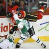 Dallas Stars\' Sergei Gonchar, right, from Russia, upends Calgary Flames\' David Jones during first-period NHL hockey game action in Calgary, Alberta., Thursday, Nov. 14, 2013. (AP Photo/The Canadian Press, Jeff McIntosh)