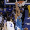 Photo - New Orleans Hornets forward Anthony Davis (23) dunks in front of Golden State Warriors center Andrew Bogut (12), from Australia, during the second quarter of an NBA basketball game in Oakland, Calif., Wednesday, April 3, 2013. (AP Photo/Jeff Chiu)