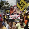 A protester holds up a picture of Venezuela\'s Vice President Nicolas Maduro that reads in Spanish
