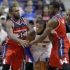 Photo - Detroit Pistons center Greg Monroe, center, is trapped in a corner by Washington Wizards forward Trevor Booker (35) and guard John Wall during the first half of a preseason NBA basketball game Tuesday, Oct. 22, 2013, in Auburn Hills, Mich. (AP Photo/Duane Burleson)