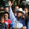 Photo - Jose Trevino Morales, center, acknowledges the crowd as he stands with the trophy after Mr. Piloto won the All American Futurity horse race in September 2010 at Ruidoso Downs, N.M. AP photo