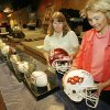 Sandi Wyn and Susan Price arrange autographed football helmets donated by OU and OSU for a benefit auction for the Wilson-Dillard family at The Bridge Assembly of God Church in Mustang, Friday, August 24, 2007. Siblings Travis Dillard and Shannon Dillard-Wilson were killed in a fireworks accident. BY DAVID MCDANIEL, THE OKLAHOMAN.