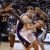 Phoenix Suns\' Goran Dragic, of Slovenia, drives past Memphis Grizzlies\' Zach Randolph (50) and Rudy Gay, right, during the second half of an NBA basketball game on Wednesday, Dec. 12, 2012, in Phoenix. (AP Photo/Matt York)