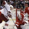 Photo - Detroit Red Wings goalie Jimmy Howard (35) stops a shot by Phoenix Coyotes wing Rob Klinkhammer, left,  in the first period of an NHL hockey game in Detroit, Monday April 22, 2013. (AP Photo/Paul Sancya)