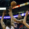 Photo - Atlanta Hawks' Mike Scott (32) shoots over Phoenix Suns' Marcus Morris during the first half of an NBA basketball game, Sunday, March 2, 2014, in Phoenix.(AP Photo/Matt York)