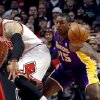 Photo - Los Angeles Lakers forward Metta World Peace (15) knocks the ball away from Chicago Bulls forward Carlos Boozer during the first half of an NBA basketball game, Monday, Jan. 21, 2013, in Chicago. (AP Photo/Charles Rex Arbogast)