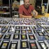 Photo - In this Aug. 25, 2014 photo, Troy Thibodeau, from Saco River Auction Co., examines a collection of more than 1,400 baseball cards from 1909, 1910, and 1911 in Biddeford, Maine. The collection will be auctioned off starting in January 2015. (AP Photo/David Sharp)