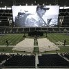Photo - A photo of Christopher Kyle is displayed on the large screen before the start of a memorial service for the former Navy SEAL at Cowboys Stadium, Monday, Feb. 11, 2013, in Arlington, Texas. Thousands are expected to attend the public memorial service for Kyle, the former Navy SEAL sniper who was shot to death at a Texas shooting range. (AP Photo/Brandon Wade)
