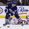 New York Rangers\' Ryan Callahan falls as Toronto Maple Leafs\' Morgan Rielly controls the puck during the first period of an NHL hockey game in Toronto, Saturday, Jan. 4, 2014. (AP Photo/The Canadian Press, Mark Blinch)