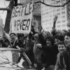 Photo - FILE - In this Feb. 7, 1964 file photo, screaming teenagers, mostly girls, wave a banner