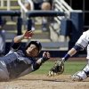Milwaukee Brewers catcher Jonathan Lucroy can\'t handle the throw as San Diego Padres\' Everth Cabrera scores from first on a single by Alexi Amarista during the second inning an exhibition baseball game Friday, March 7, 2014, in Phoenix. (AP Photo/Morry Gash)