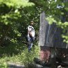 An East Cleveland police officer searches the backyard of a house Sunday, July 21, 2013, where one of three bodies were recently found, in East Cleveland, Ohio. The bodies, believed to be female, were found about 100 to 200 yards (90 to 180 meters) apart, and a 35-year-old man was arrested and is a suspect in all three deaths, though he has not yet been charged, East Cleveland Mayor Gary Norton said Saturday. (AP Photo/Tony Dejak)