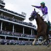 Photo - Victor Espinoza rides California Chrome to victory during the 140th running of the Kentucky Derby horse race at Churchill Downs Saturday, May 3, 2014, in Louisville, Ky.  (AP Photo/David J. Phillip)