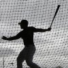 Photo - Oakland Athletics invitee catcher Bruce Maxwell hits in a batting cage as rain begins to fall before the Oakland Athletics are scheduled to play the Texas Rangers in a spring training baseball game Saturday, March 1, 2014, in Phoenix. (AP Photo/Gregory Bull)
