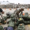 Soldiers hurriedly search for their bags so they can fall into formation with fellow troops. A US Army spokesman from Ft. Sill said nearly 1,000 troops boarded buses for the trip to Will Rogers World Airport in Oklahoma City to catch flights home for the Christmas holidays. Buses filled with soldiers began arriving at the airport after midnight Wednesday and into the pre-dawn hours on Thursday, Dec. 19, 2013. While waiting to board flights, the troops were treated to food and warm beverages at the YMCA Military Welcome Center at the airport. Soldiers were offered pizza, doughnuts and sub sandwiches, with hot coffee or chocolate, and bottled water. Friendly faces from local organizations were there to greet them and assist them. Volunteers represented several groups, including Blue Star Mothers, Patriot Guard Riders and an organization consisting of Purple Heart recipients. Photo by Jim Beckel, The Oklahoman