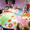 """Children bounce stuffed monkeys on a parachute in the """"Music with Susan"""" class at Edmond Public Library. PHOTOS BY DAVID MCDANIEL, THE OKLAHOMAN"""
